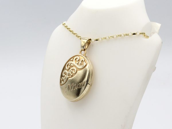a gold engraved oval locket on a gold chain