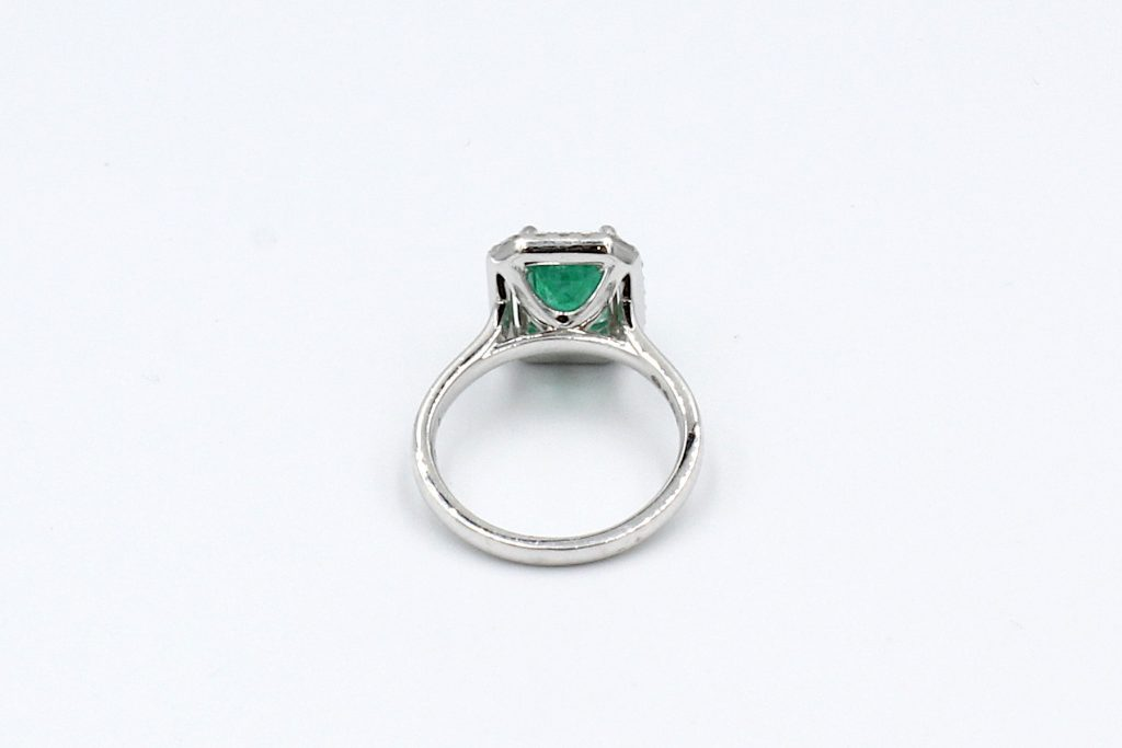 rear view of an emerald and diamond halo engagement ring made from platinum.