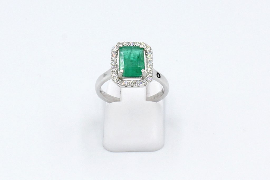 front view of an emerald and diamond halo engagement ring made from platinum.