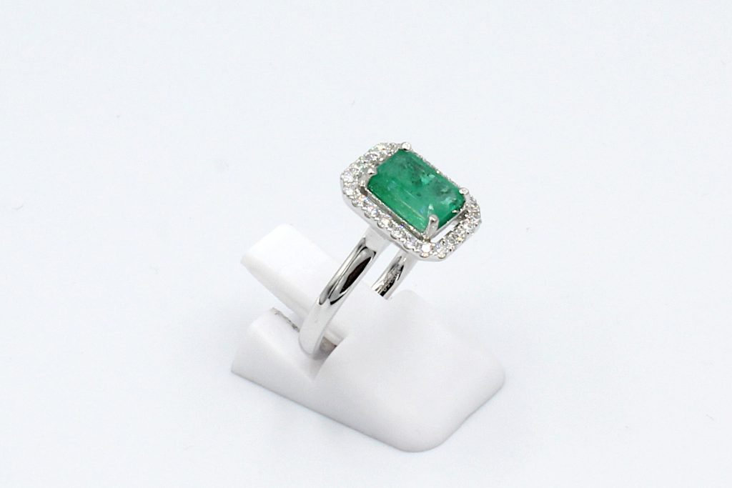 side view of an emerald and diamond halo engagement ring made from platinum.