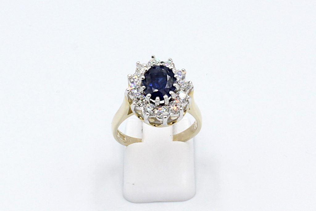 front view of a sapphire and diamond cluster ring made from gold