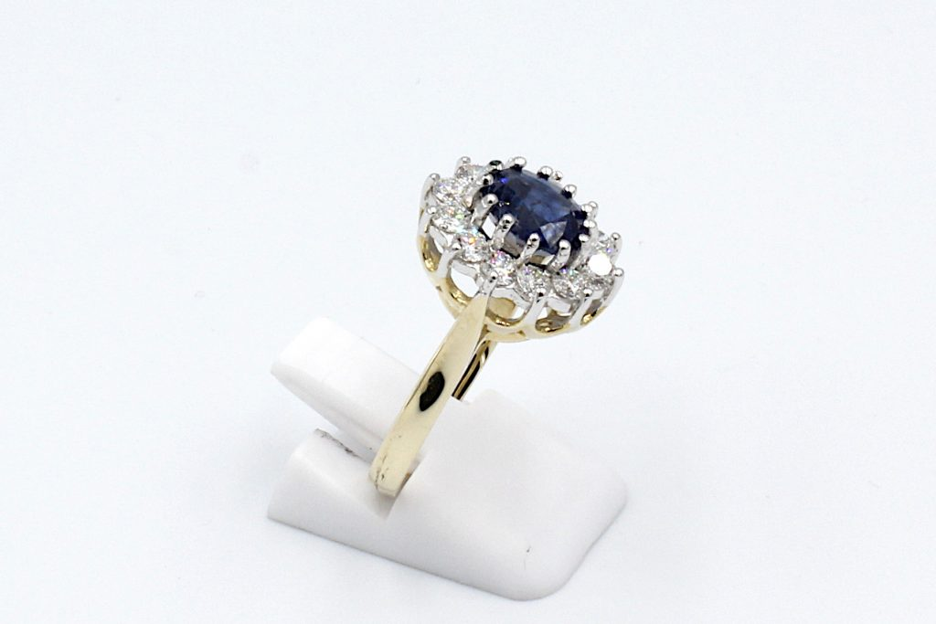 side view of a sapphire and diamond cluster ring made from gold