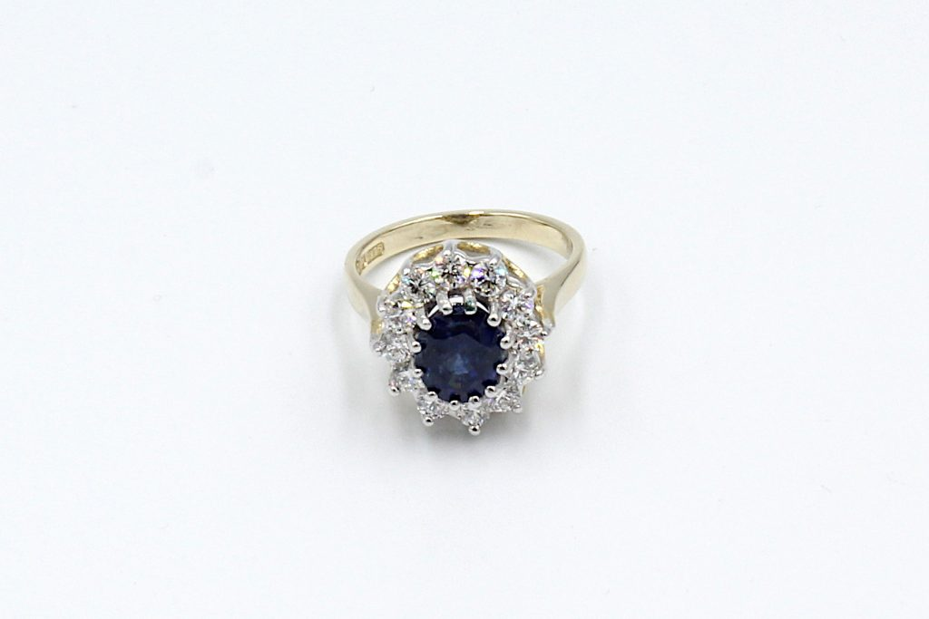 top view of a sapphire and diamond cluster ring made from gold