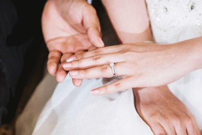 groom holding brides hand with ring on finger